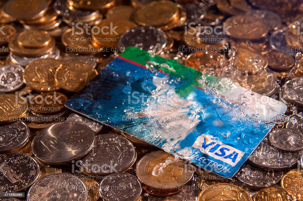 Credit card on a pile of coins in the rain stock photo
