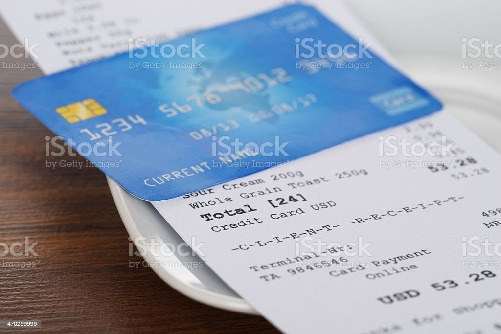 A credit card on top of a printed receipt stock photo