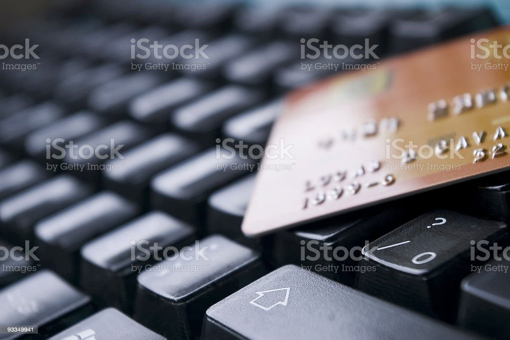 Credit card resting on computer keyboard showing E-Commerce royalty-free stock photo