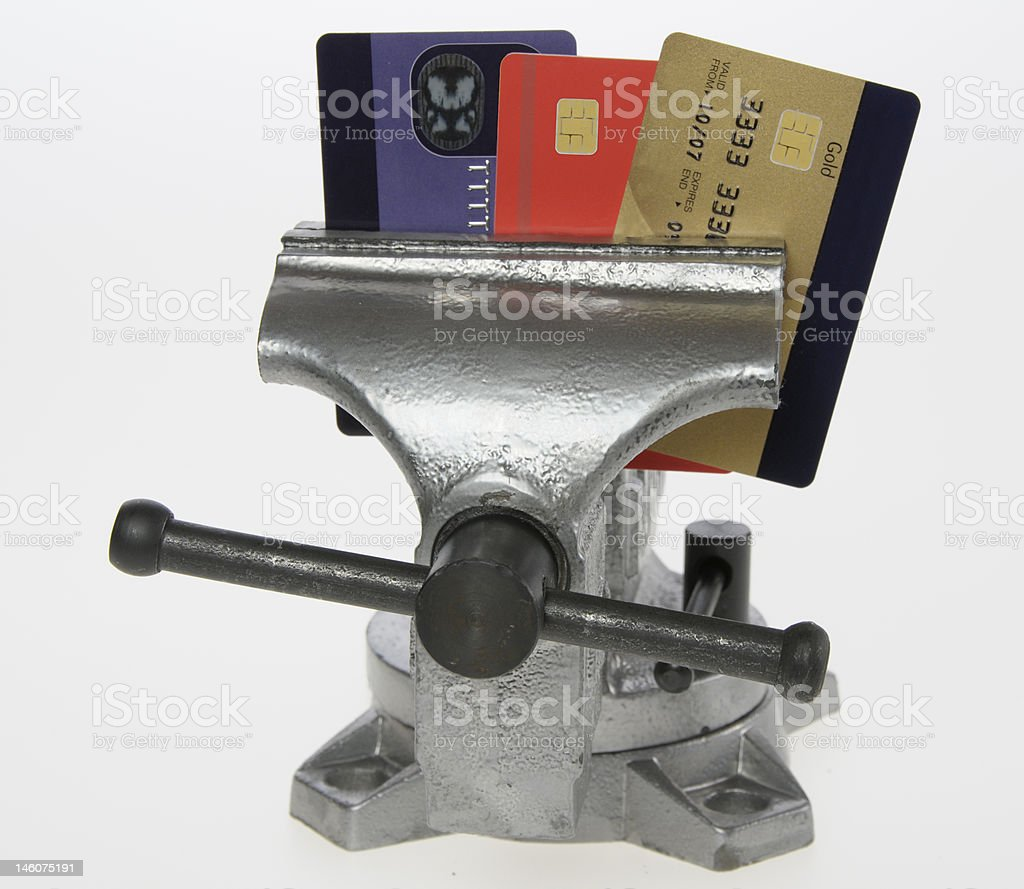 Credit cards being squeezed in  a vice royalty-free stock photo