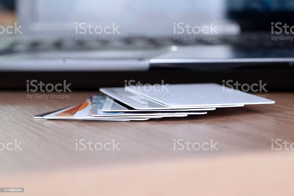 Credit cards  on a table and  a laptop behind stock photo