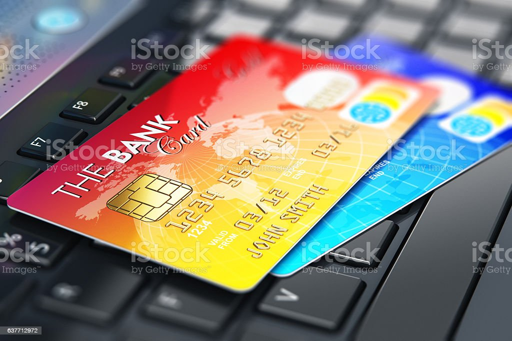 Credit cards on laptop keyboard stock photo