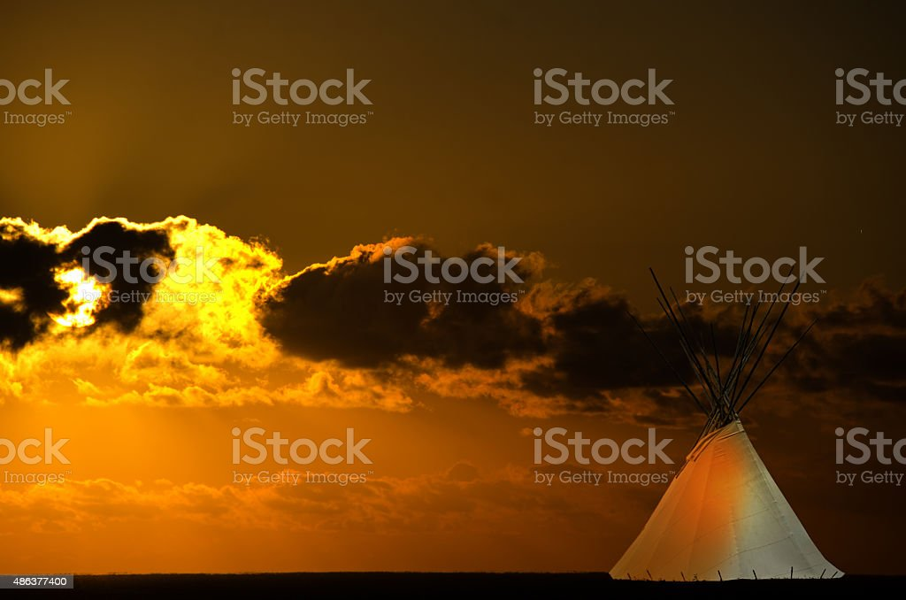 Cree teepee and a golden prairie sunset stock photo
