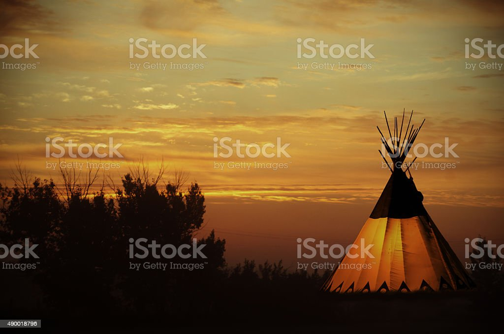 Cree teepee and golden prairie sunset- old photo effect stock photo