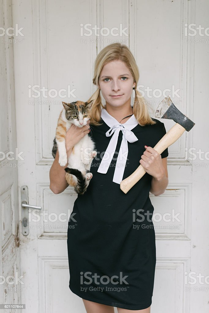 Creepy blond woman with axe and cat stock photo