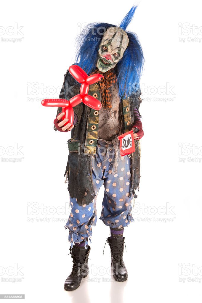 Creepy Clown holding a ballon animal and pop gun stock photo