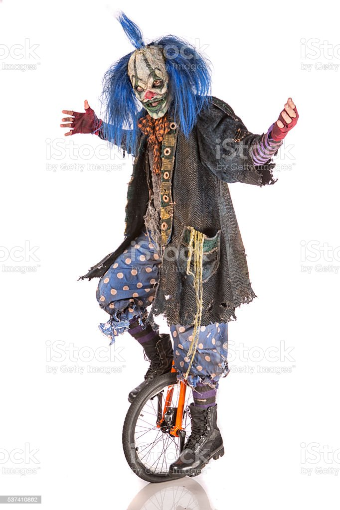 Creepy Clown riding unicycle stock photo