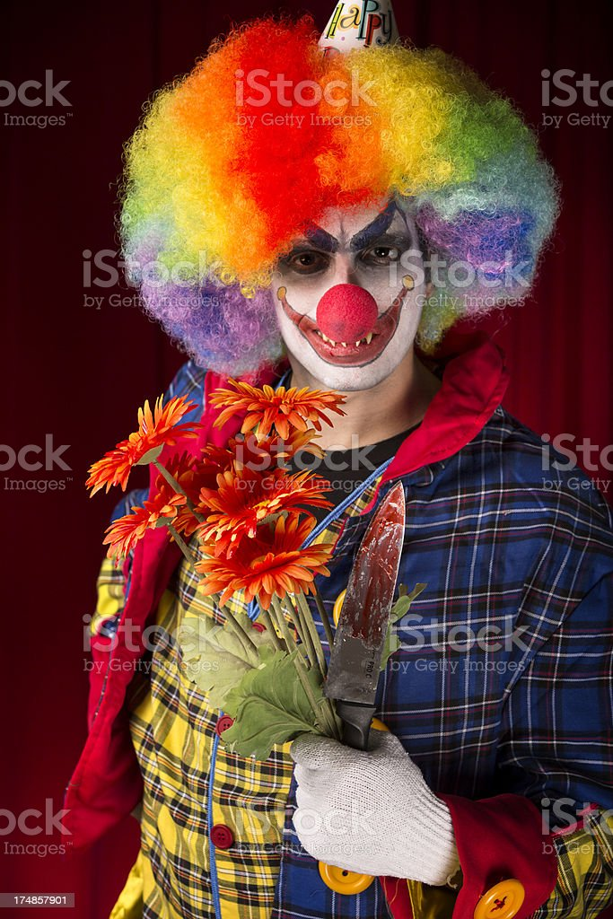 Creepy Clown with a bloody knife and flowers royalty-free stock photo