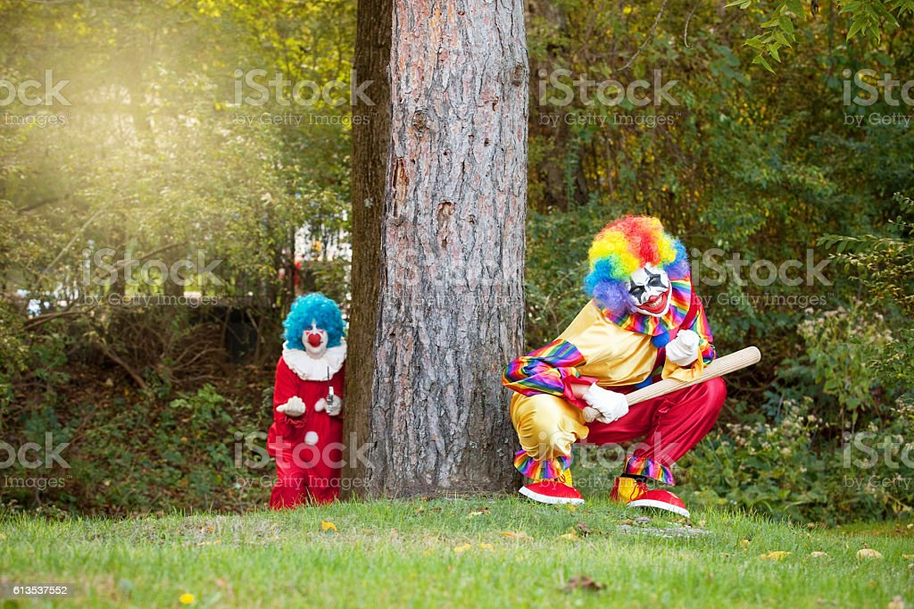 Creepy Clowns Luring People Into Woods stock photo