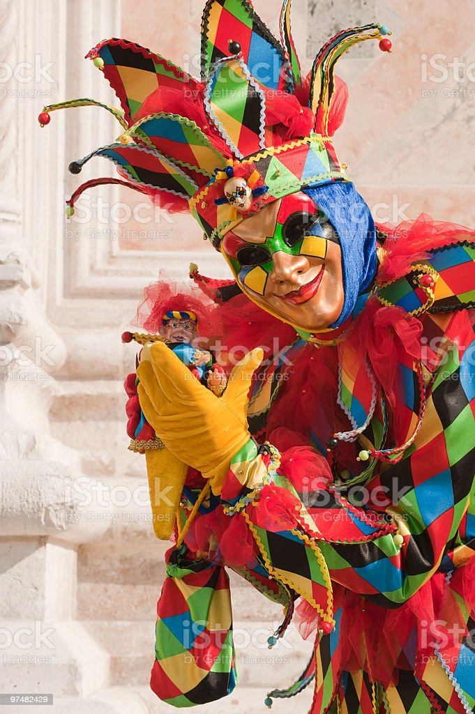 Creepy jester wearing carnival of masks stock photo