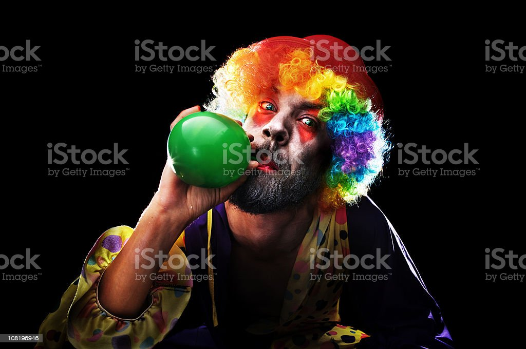 Creepy Looking Clown Blowing up Balloon on Black Background stock photo