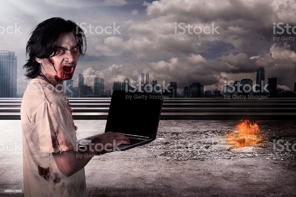 Creepy male zombie typing with laptop stock photo