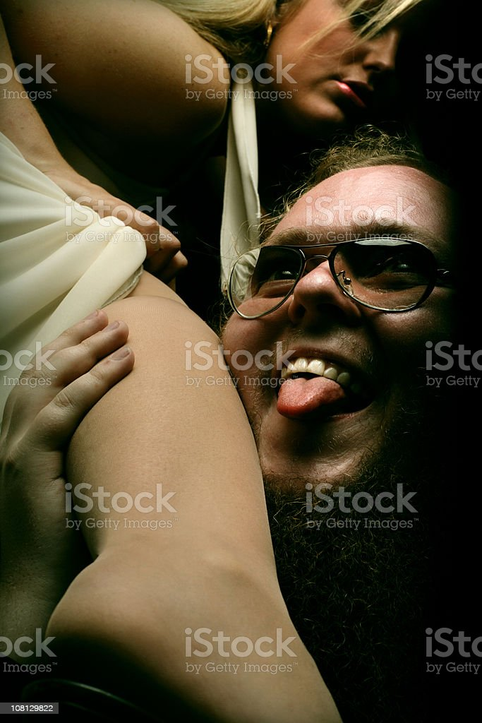 Creepy Man Licking Young Woman's Leg, Low Key royalty-free stock photo