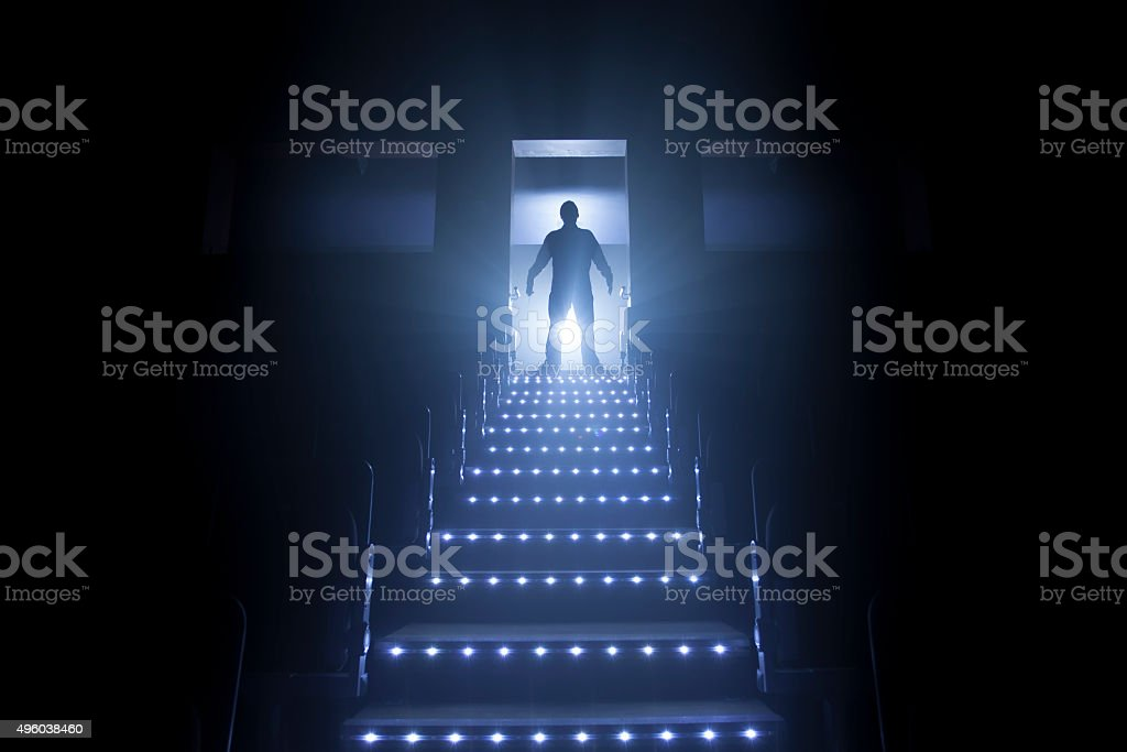Creepy maniac figure at the top of the stairs stock photo