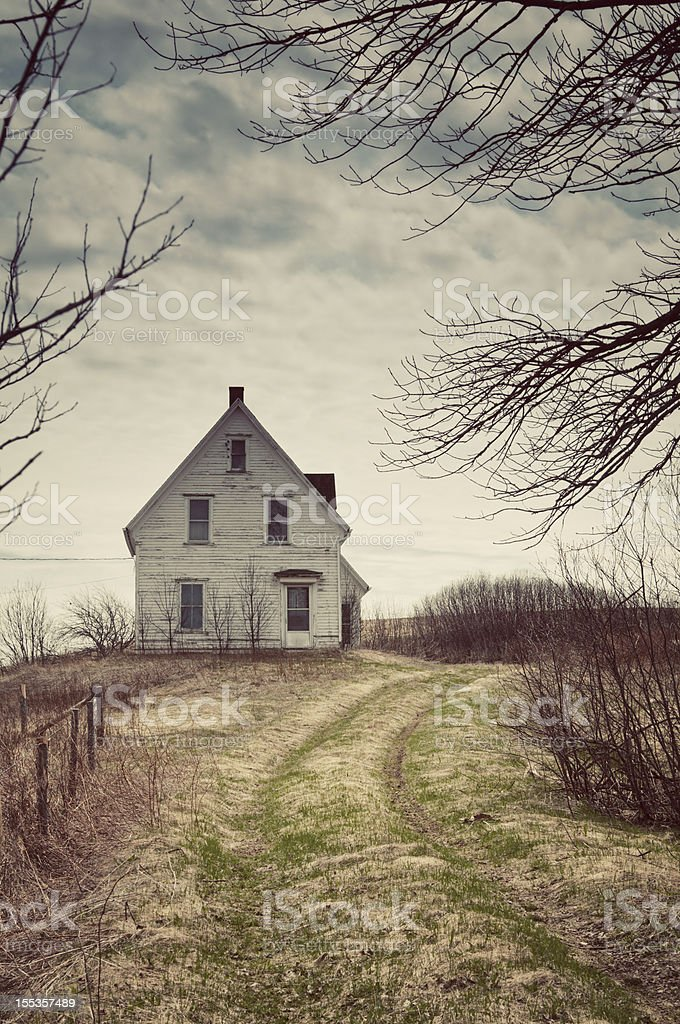 Creepy old house on a hill at the end of a driveway stock photo