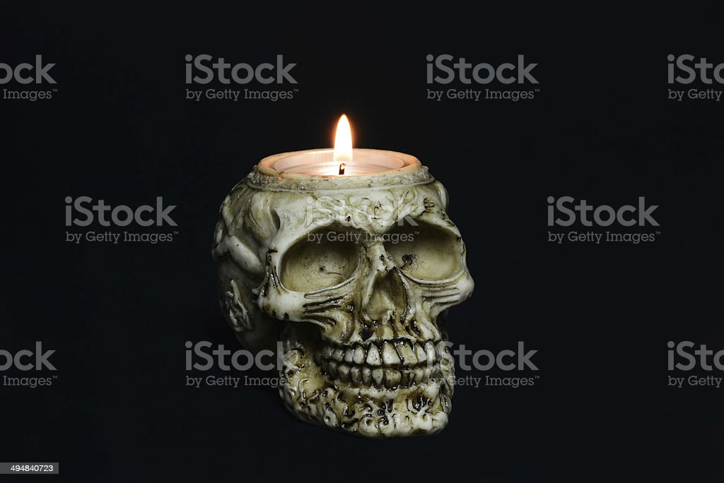 creepy skull candle on black background - half turn royalty-free stock photo
