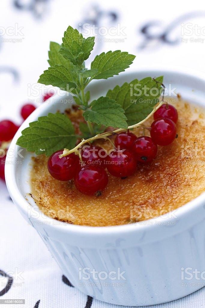 Creme Brulee with sauce and red Currants royalty-free stock photo