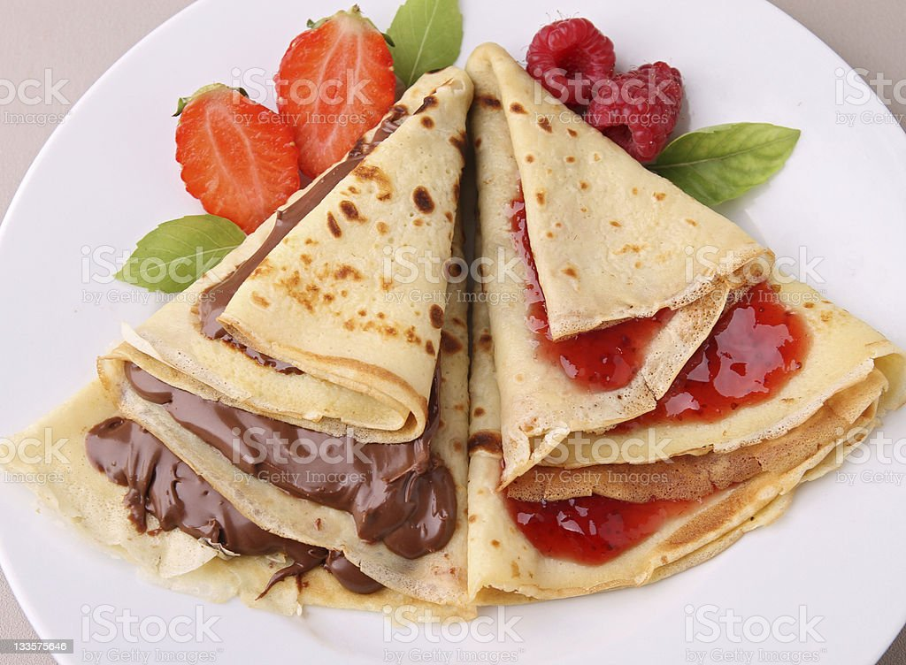 Crepe pancake with fruit and chocolate topping stock photo
