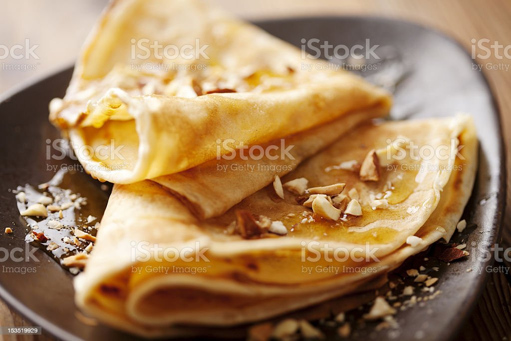 Crepes on a brown plate with syrup and nuts stock photo
