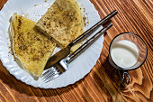 Crepes pancakes with honey and walnuts and glass of milk