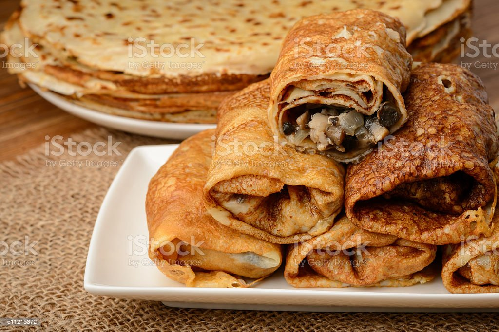 Crepes stuffed with chicken and mushrooms on wooden table. stock photo