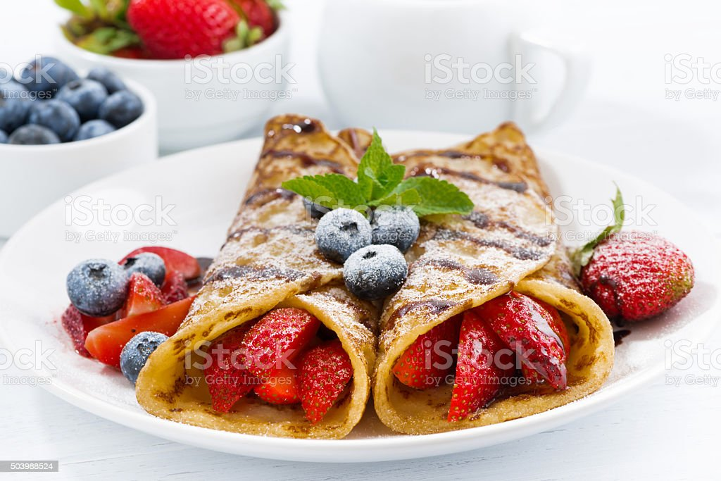 crepes with berries and chocolate sauce for breakfast on plate stock photo
