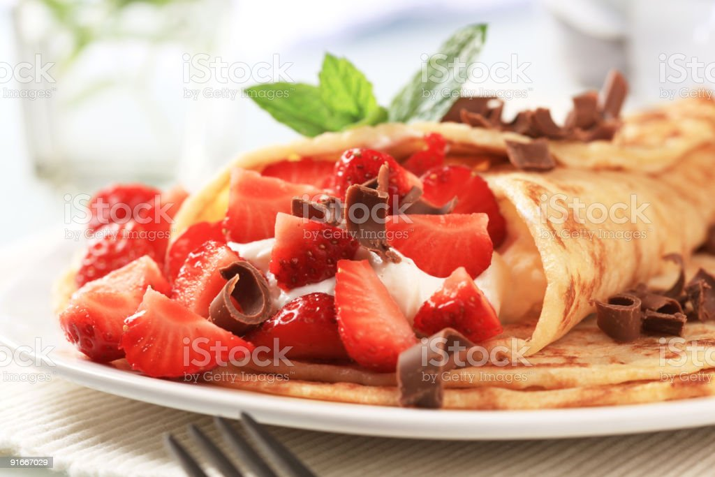 Crepes with curd cheese and strawberries stock photo