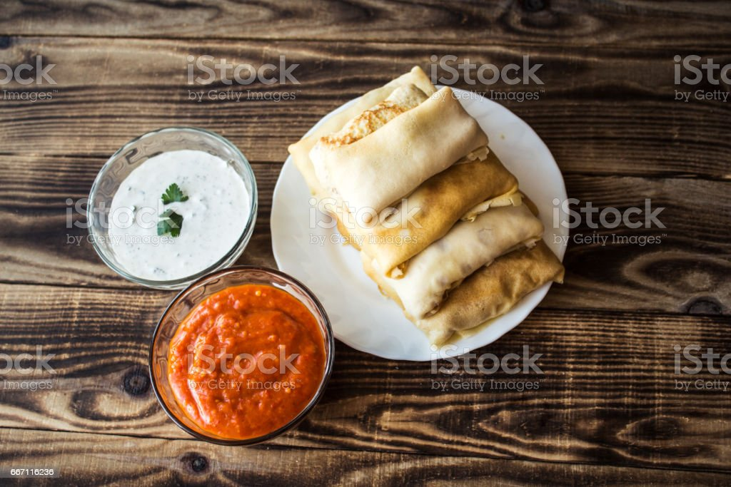 crepes with stuffing and white sauce and tomato stock photo