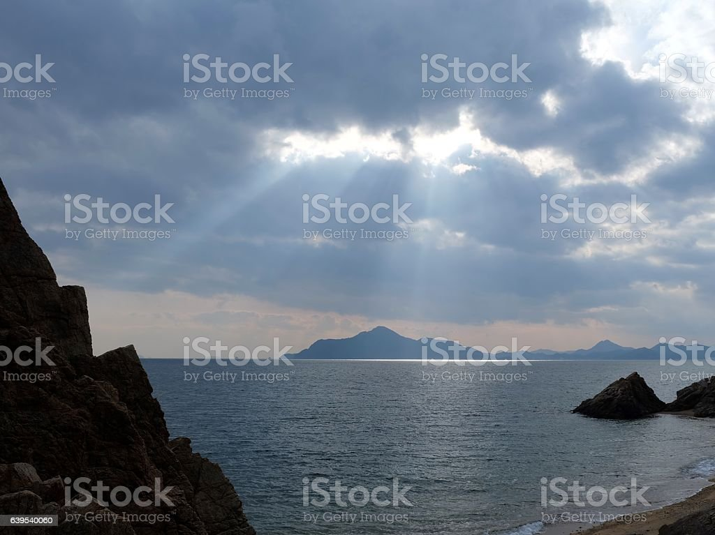 Crepuscular rays on island stock photo
