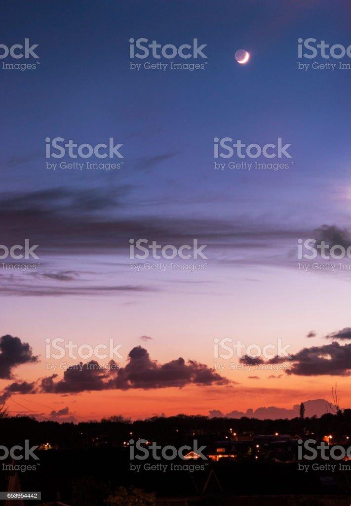 Crescent moon at sunset stock photo