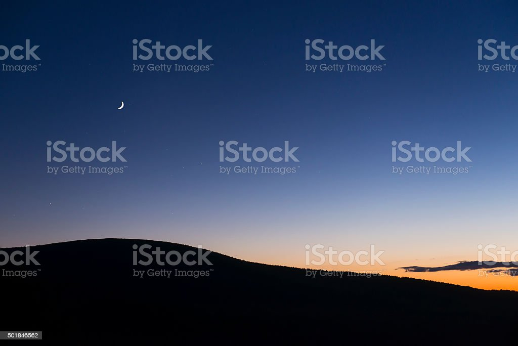 Crescent Moon at Sunset with Colorful Sky stock photo