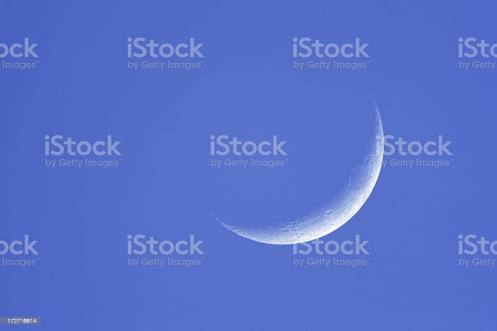 Crescent moon in daylight stock photo