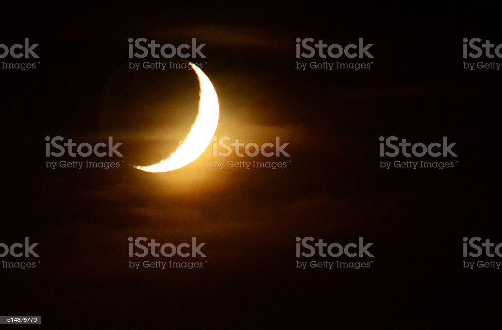 crescent moon in night sky lit up stock photo