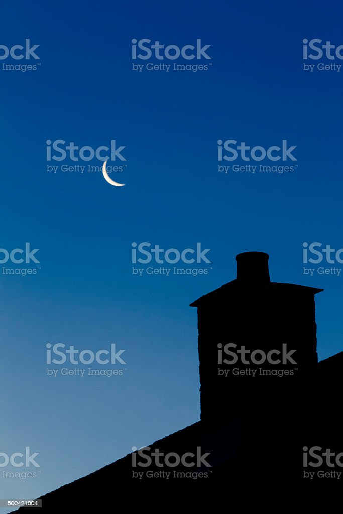 Crescent moon in pre-dawn sky stock photo