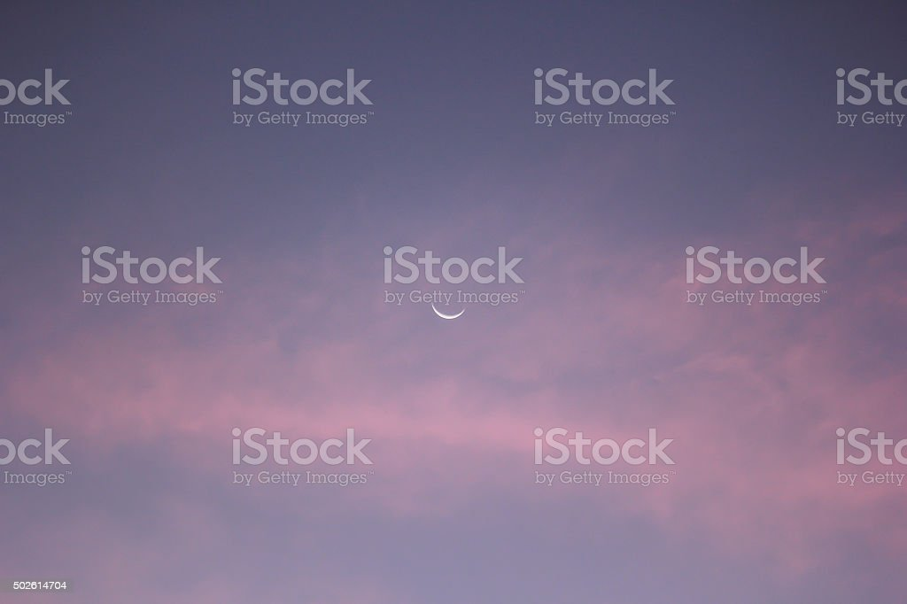 Crescent moon on blue sky stock photo