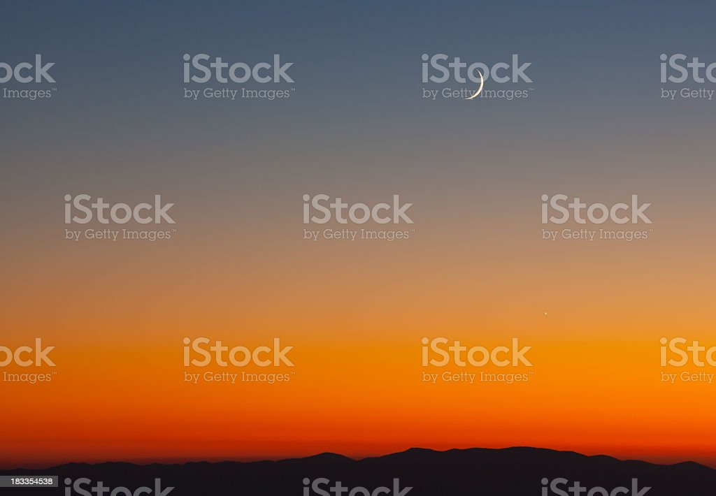 Crescent moon over a mountain at sunset stock photo
