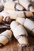 crescent rolls with poppy seeds macro on a plate. vertical
