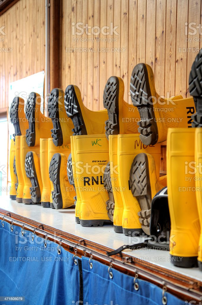 RNLI crew wellington boots lined up in readiness stock photo