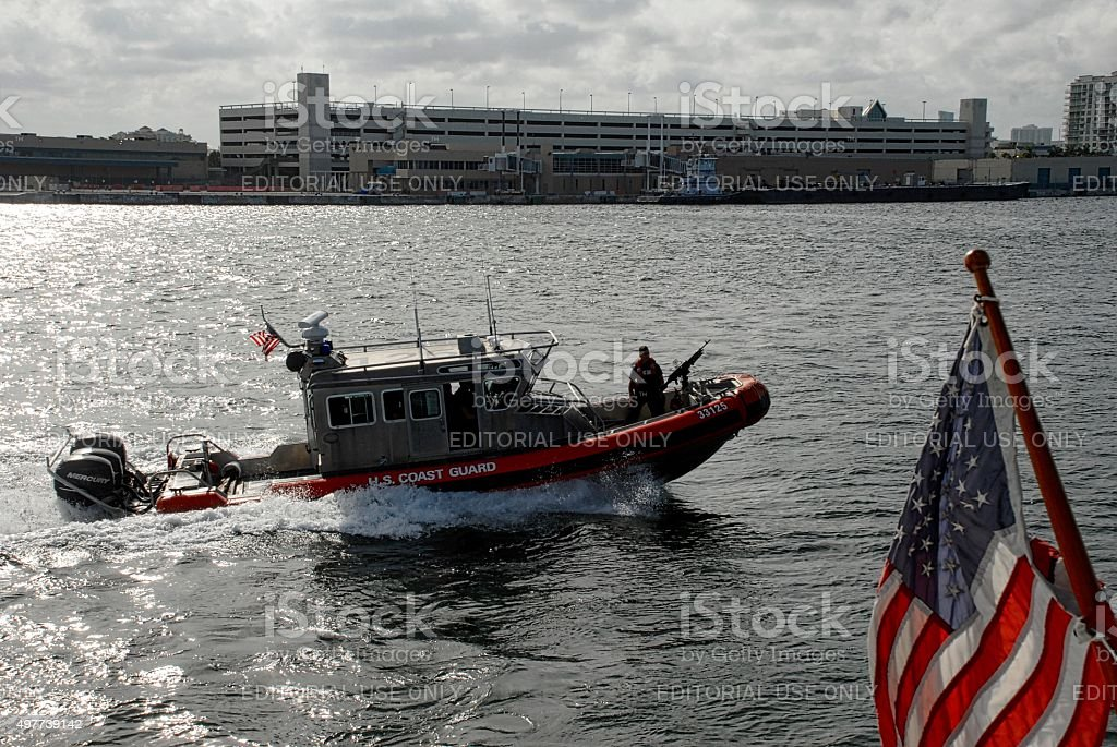 Crewman mans machine gun aboard U.S. Coast Guard boat stock photo