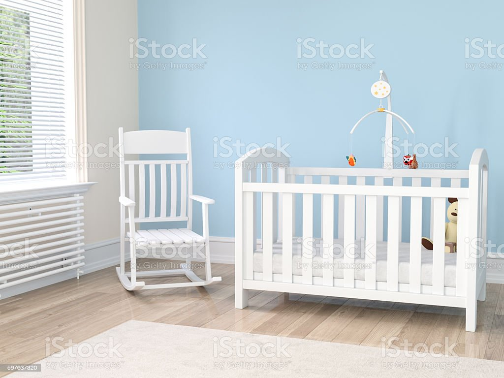 Crib in nursery with rocking chair stock photo