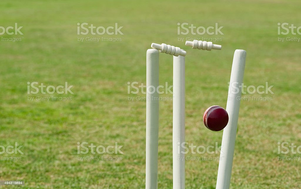 Cricket ball hitting stumps stock photo
