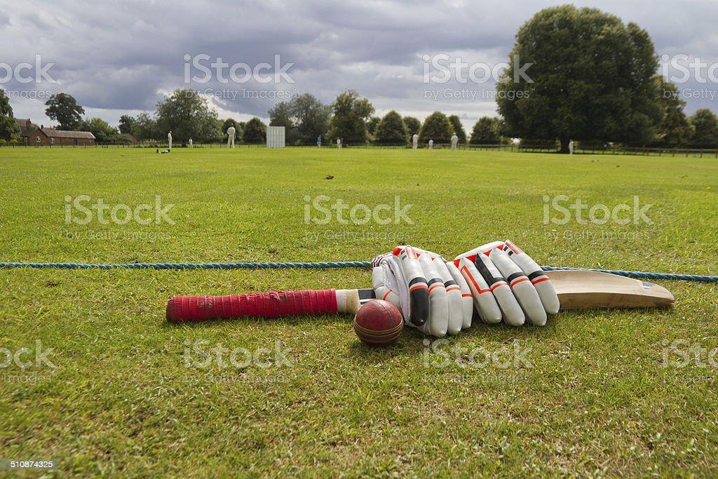 Cricket bat and gloves on English village green. stock photo