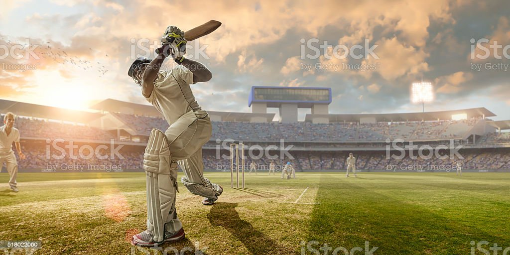 Cricket Batsman Hitting Ball During Cricket Match In Stadium stock photo