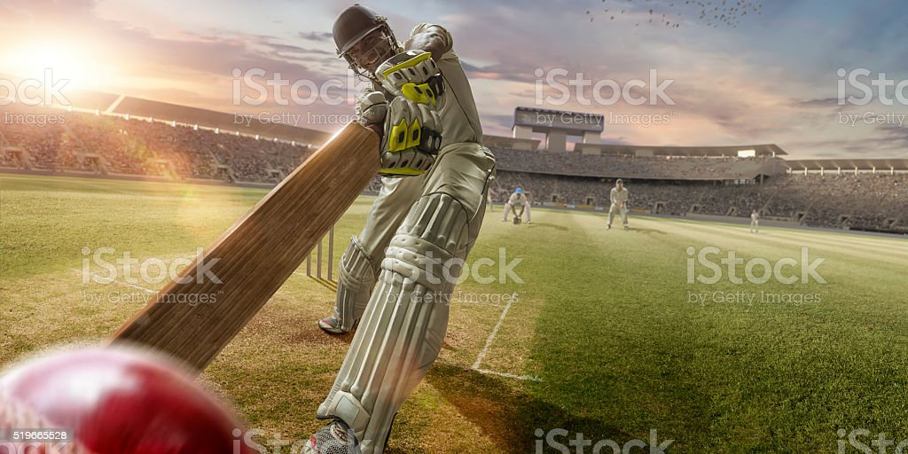 Cricket Batsman Hitting Ball During Cricket Match In Stadium stock photo