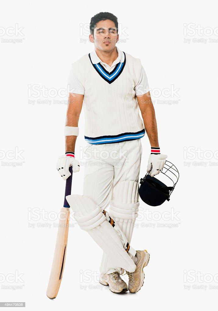 Cricket batsman holding a bat and helmet stock photo