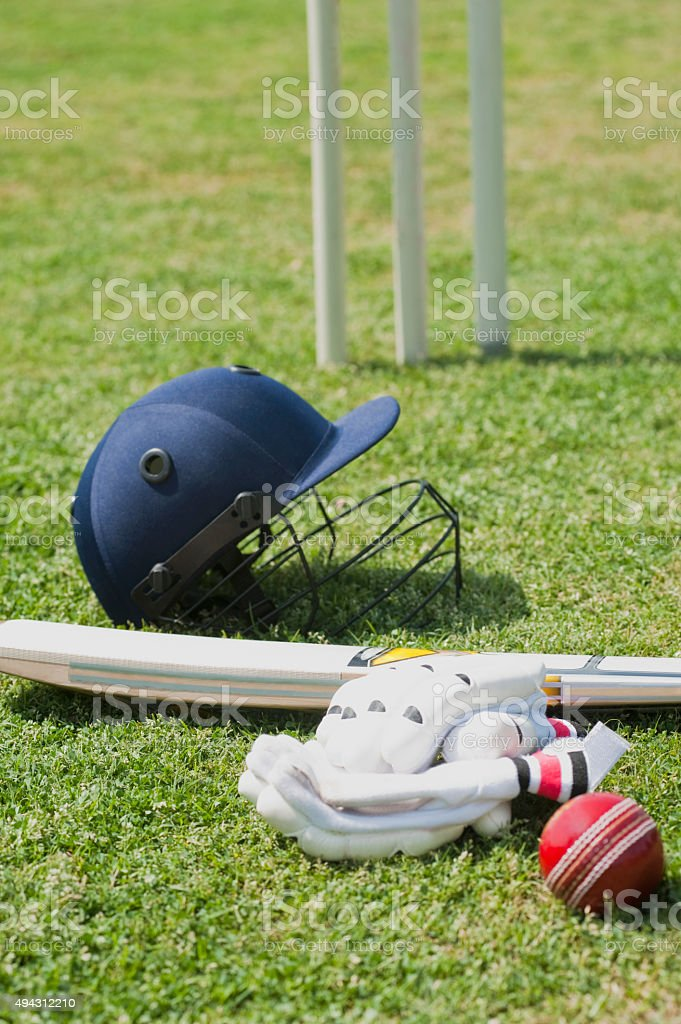 Cricket batting gears in a field stock photo