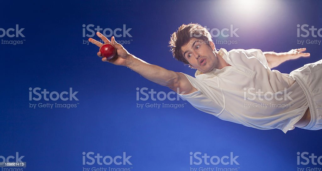 Cricket player catching ball stock photo