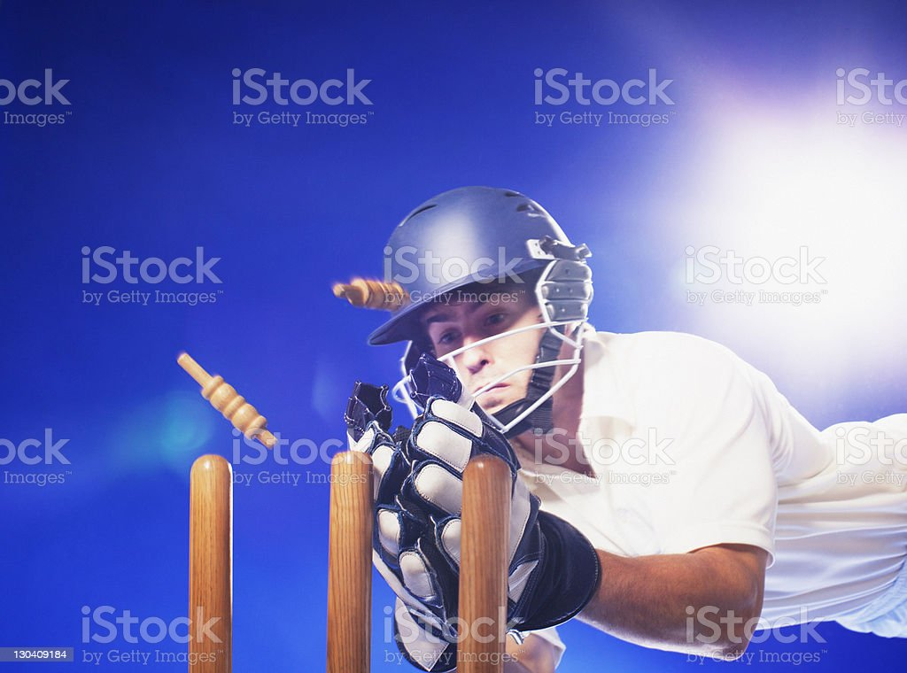 Cricket player reaching for bats stock photo