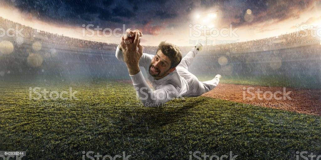 Cricket outfilder catches a ball. He is wearing unbranded sports...