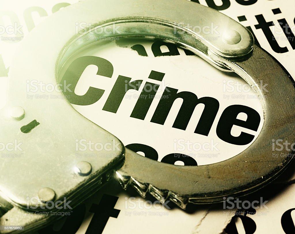 Crime headline circled by worn handcuff stock photo